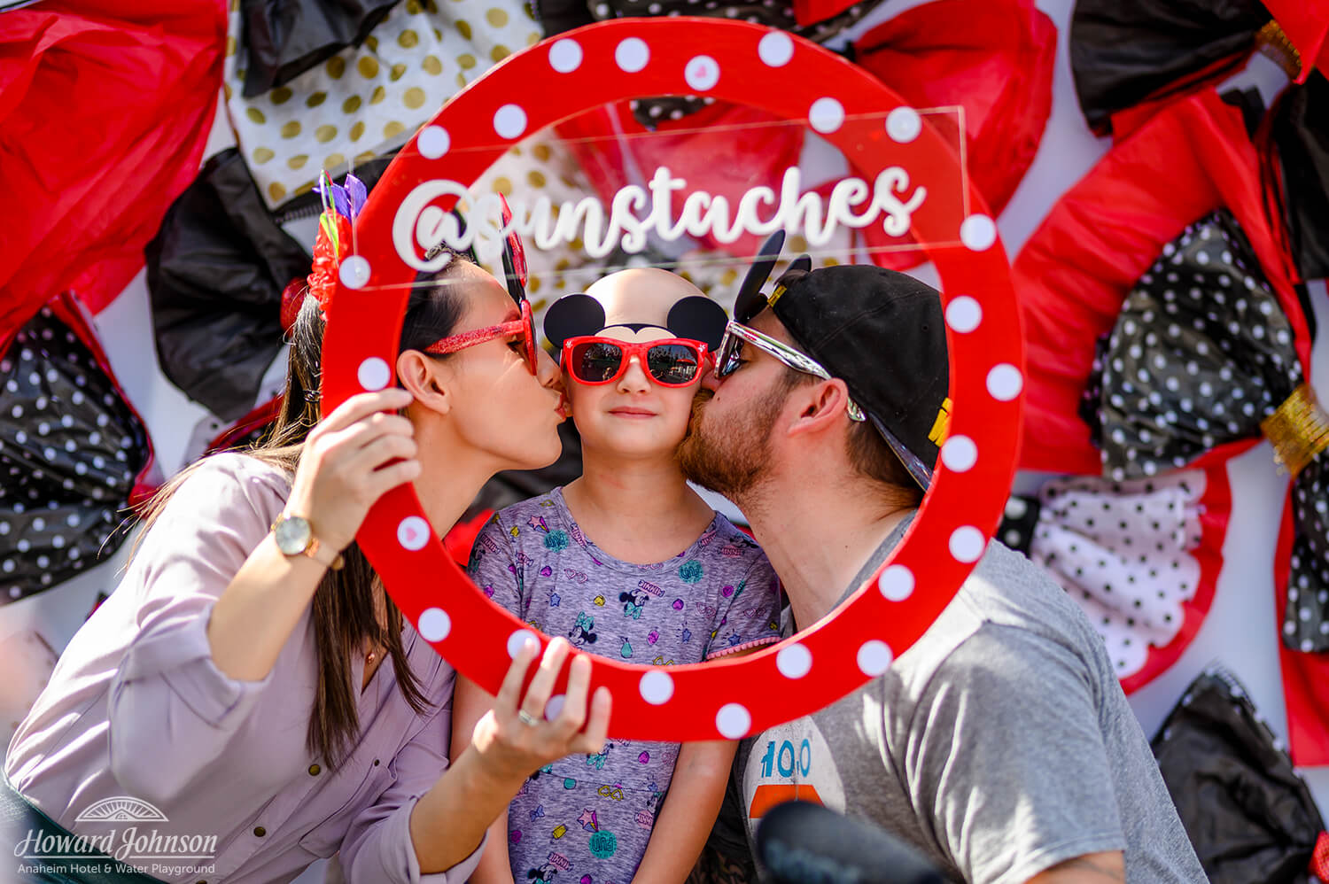 a mother and father give their daughter a kiss on the cheek while posing for a photo with a circular polka dot frame and social media handle