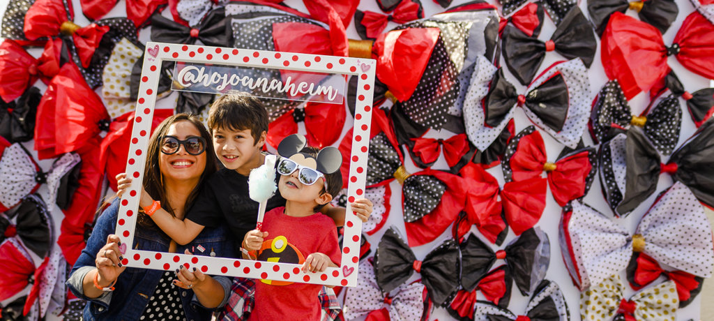 A woman and two boys pose for a picture with a wooden pokadot picture frame with the @hojoanaheim social media handle on it