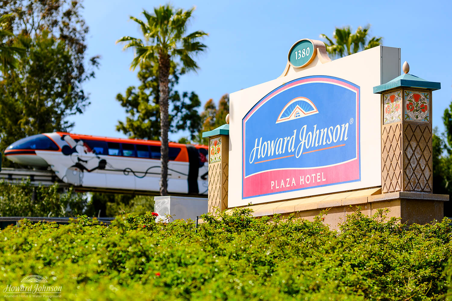 A Disneyland tram passes by a sign for the Howard Johnson Anaheim hotel