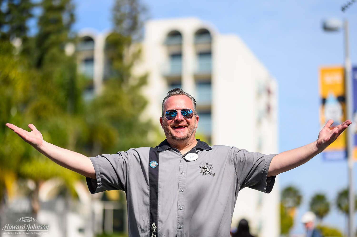 A man wearing sunglasses and a Disneyland shirt holds his hands in the air and smiles, pictured in front of the Howard Johnson Anaheim hotel