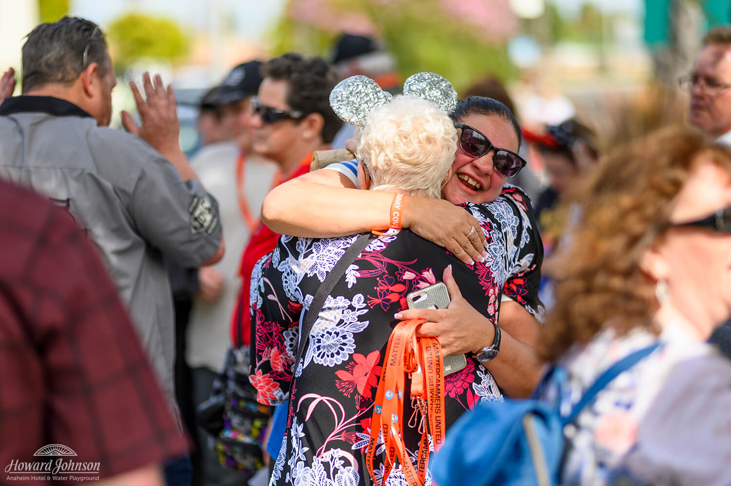 two women who are a part of the Mattercammers United embrace in a hug in the middle of a crowd of people