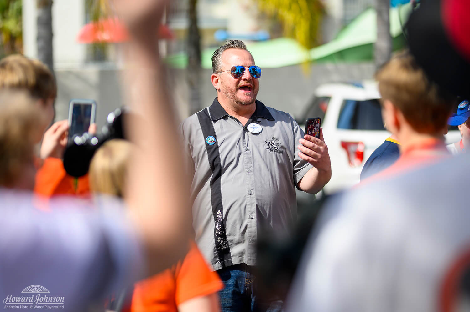 A man wearing sunglasses with his phone in his hands leads a group of people known as Mattercammers United