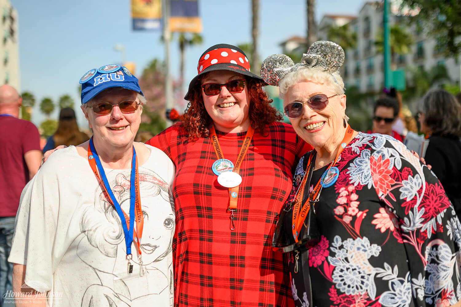 Three women wearing Disney hats and lanyards smile for the camera