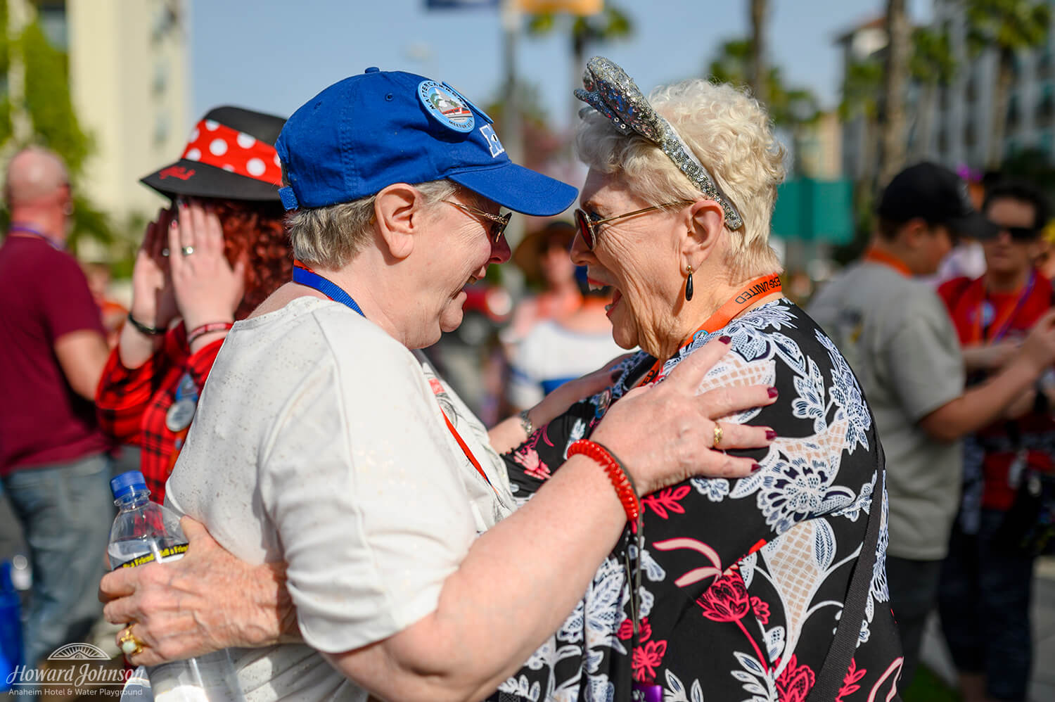 Two women wearing disney hats embrace in a hug and smile