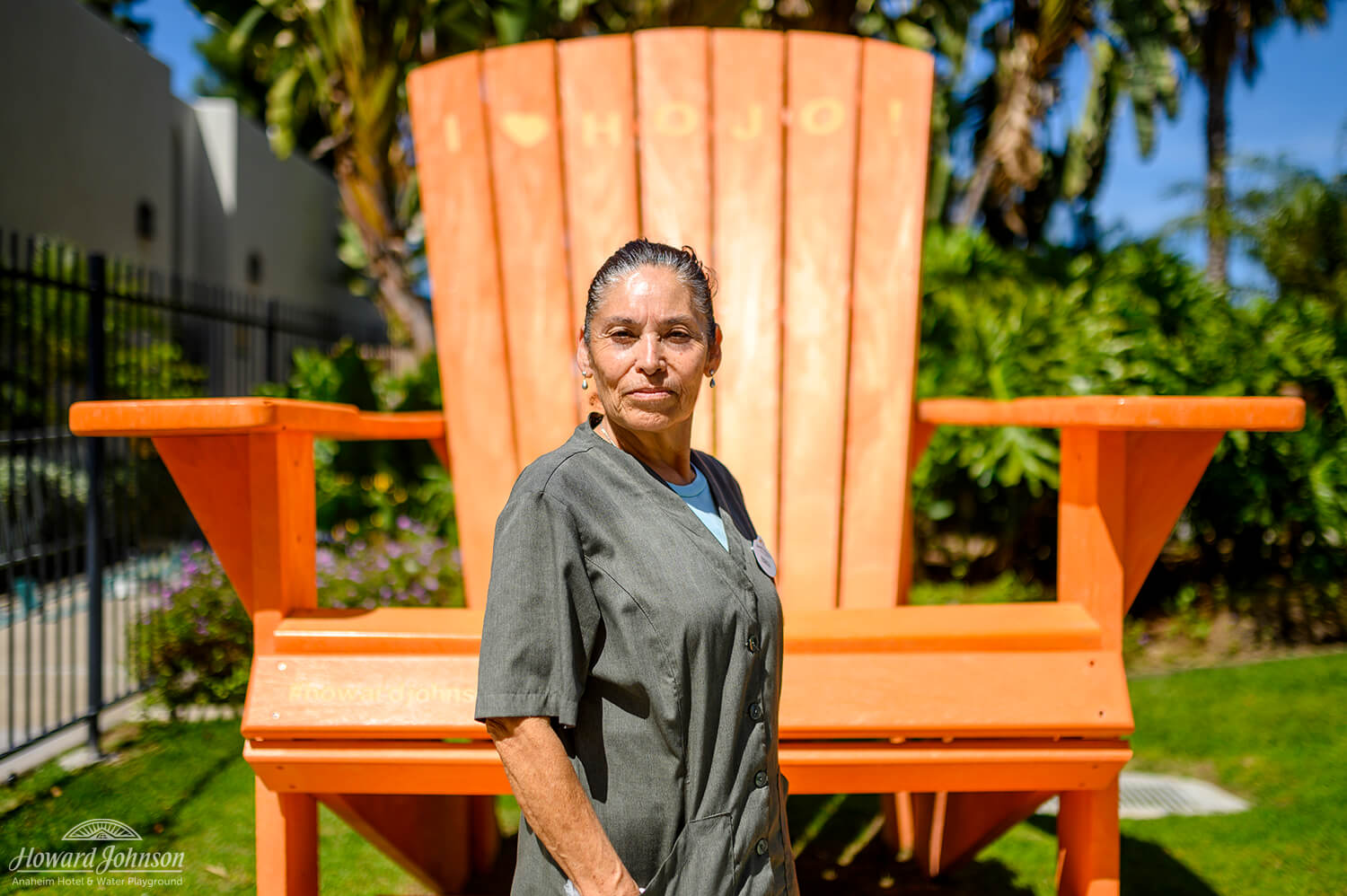 A Howard Johnson Anaheim employee named Teresa poses outside the hotel in front of a large orange Adirondack chair