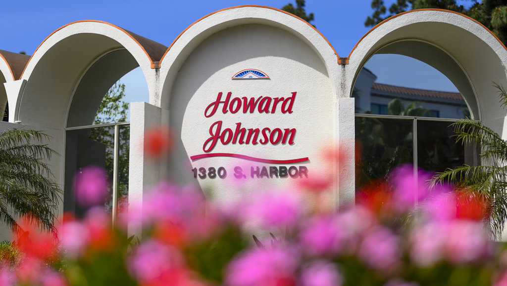 A close up of the Howard Johnson Anaheim hotel with pink flowers blurred in the foreground